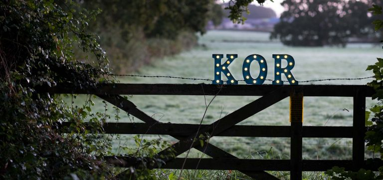 KOR light-up letters on a fence in the countryside