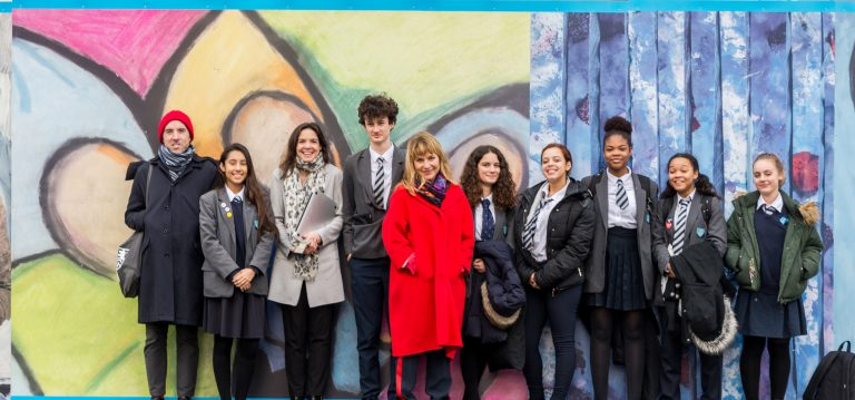 students and teachers stand beside their artwork on Hackney New Primary School hoardings