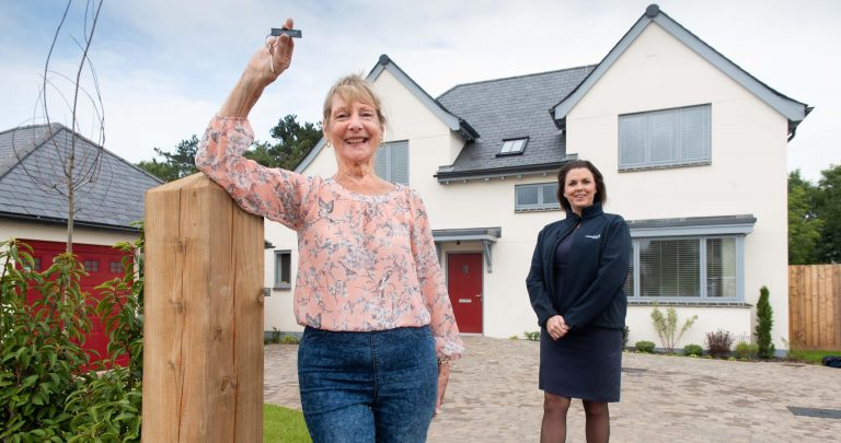 Jan Lewis outside her new Cavanna home at Wolborough Hill with Sales Advisor Sarah Bowden